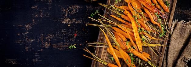 Carote biologiche al forno con timo, miele e limone. alimenti biologici vegani. banner.