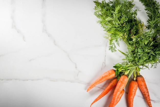 Carote crude dell'agricoltore organico fresco con le foglie su un tavolo da cucina di marmo bianco. vista dall'alto