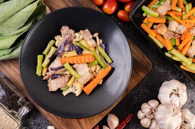 Carote e cetrioli saltati in padella con pancetta di maiale.