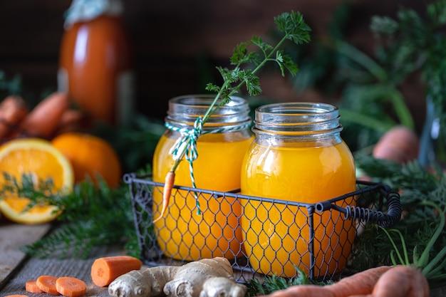 Carote e succo di carota con zenzero arancione in un barattolo di vetro in un cestino di metallo