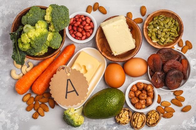 Carote, noci, broccoli, burro, formaggio, avocado, albicocche, semi, uova. sfondo bianco, vista dall'alto
