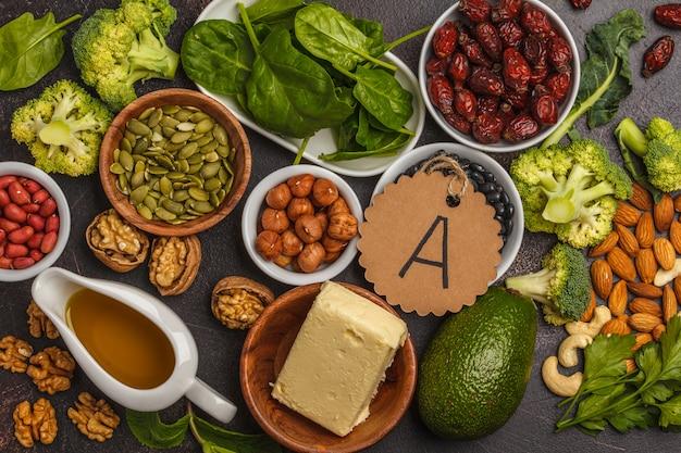Carote, noci, broccoli, burro, formaggio, avocado, albicocche, semi, uova. sfondo scuro, vista dall'alto