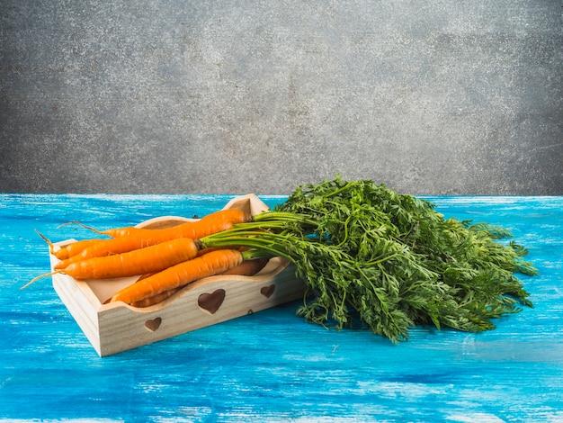 Carote organiche fresche in vassoio su superficie di legno blu