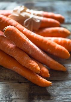 Carote organiche fresche, un mazzo di carote che si trovano sui bordi di legno