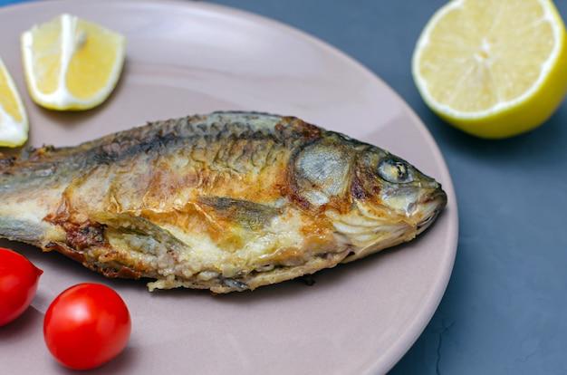 Carpa crocian appetitosa fritta del pesce con condimento su un piatto beige su una tavola grigia decorata con le fette di pomodoro e di limone. dieta mediterranea. concetto di mangia sano.
