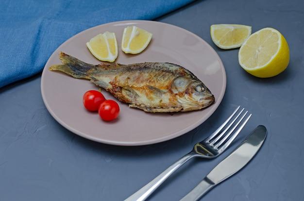 Carpa crociata appetitosa fritta del pesce con condimento su un piatto beige su una tavola grigia decorata con le fette di pomodoro e di limone con un coltello e una forchetta. concetto di mangia sano.