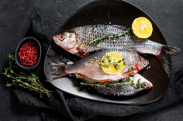 Carpa crucian con limone e timo su un piatto nero. pesce biologico di fiume. vista dall'alto