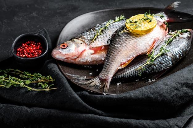 Carpa crucian cruda con limone e timo su una banda nera. pesce biologico di fiume. vista dall'alto