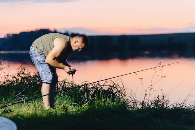 Carpa di cattura del pescatore nel lago nell'ora legale alla sera