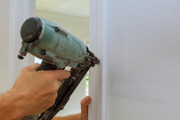 Carpenter brad usando la pistola sparachiodi alle modanature sulle porte,