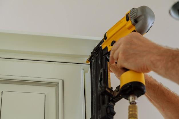 Carpenter brad utilizzando la pistola sparachiodi a crown molding su mobili da cucina che incorniciano finiture,