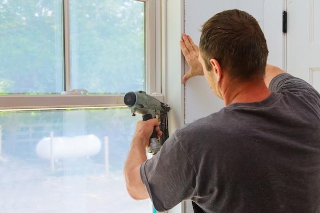 Carpenter che usa la pistola sparachiodi per modanature su finestre, cornici per cornici,