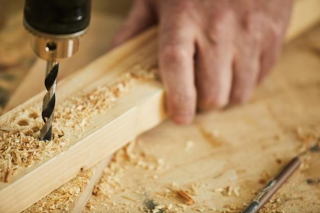 Carpenter drilling wood close in su