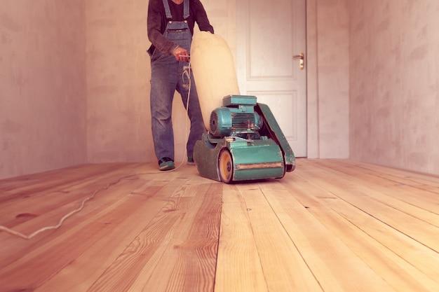 Carpenter lavora con una macchina elettrica per la macinazione del legno in una stanza