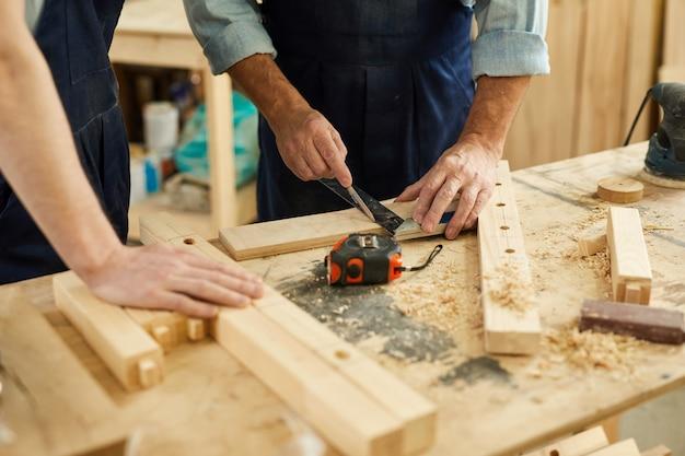 Carpenter teaching apprentice closeup