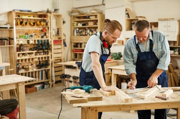 Carpenter teaching apprentice