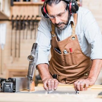 Carpentiere al lavoro con la sega