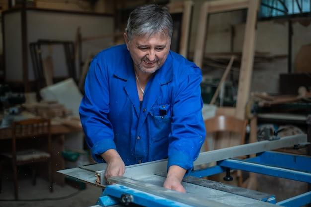 Carpentiere al lavoro nel suo laboratorio, lavorazione del legno su una macchina per la lavorazione del legno