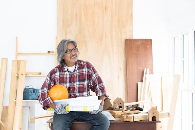 Carpentiere asiatico dell'uomo che lavora alla tavola di falegnameria nel negozio domestico di carpenteria