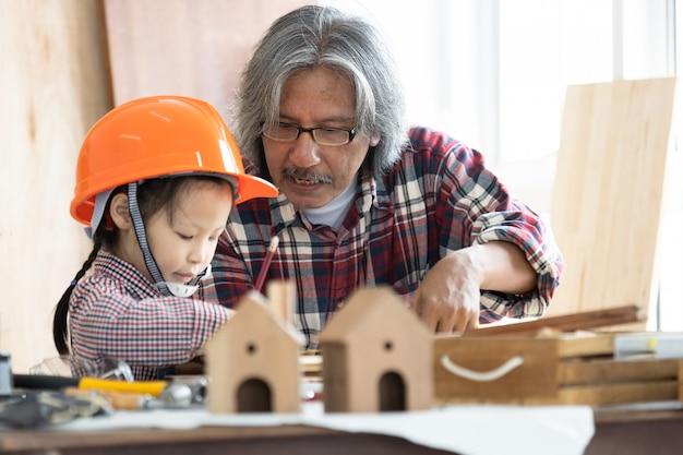Carpentiere asiatico e figlia che lavorano alla tavola di falegnameria nel negozio di carpenteria domestico