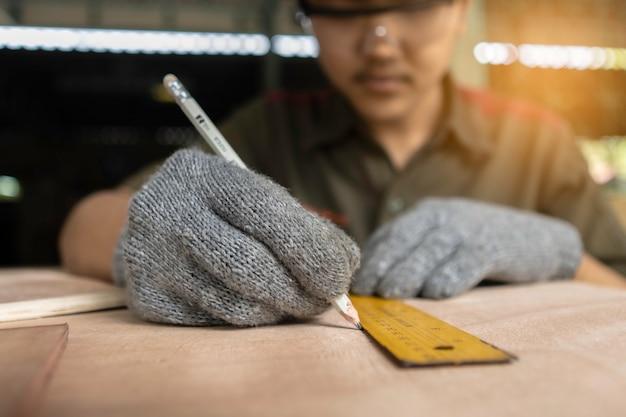 Carpentiere che lavora alle macchine per la lavorazione del legno in falegnameria. esperto falegname che taglia un pezzo di legno nel suo laboratorio di falegnameria.