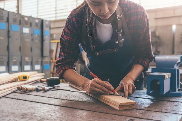 Carpentiere che lavora con l'attrezzatura sulla tavola di legno nel negozio di carpenteria. la donna lavora in un negozio di falegnameria.
