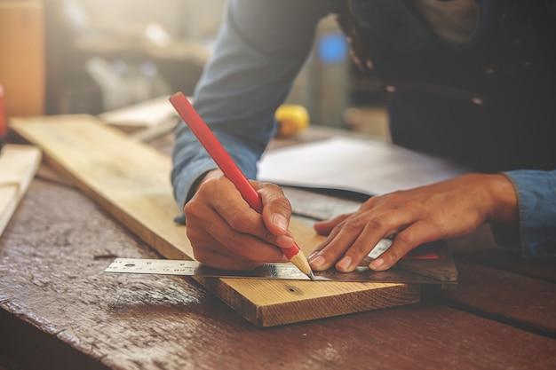 Carpentiere che lavora su macchine per la lavorazione del legno nel negozio di falegnameria.