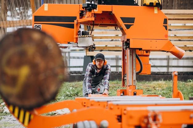 Carpentiere che lavora su una segheria su una fabbricazione di legno