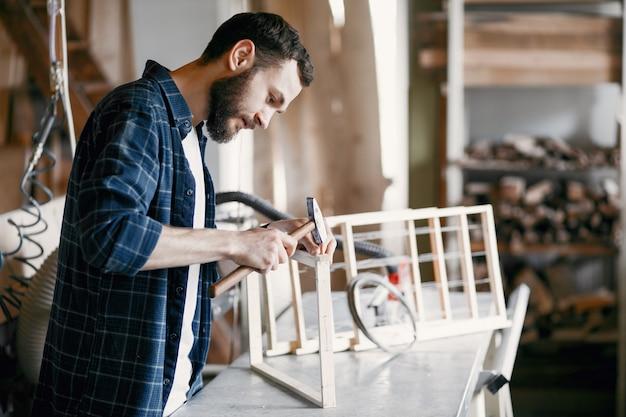 Carpentiere che martella un chiodo in un'officina