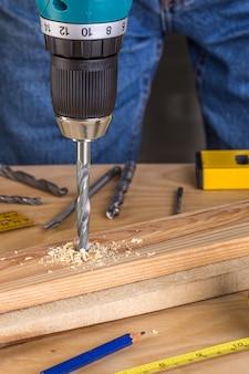 Carpentiere che perfora legno usando la perforatrice portatile