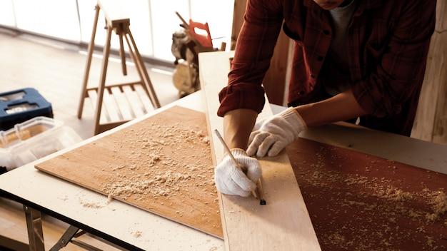 Carpentiere che utilizza la misura di nastro per ridimensionare la dimensione della scheda.