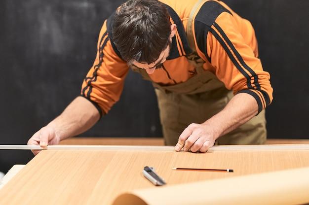 Carpentiere con salopette che segna un legno con una matita e una guida nel suo laboratorio di casa