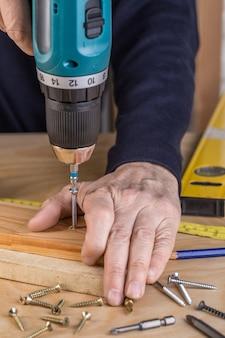 Carpentiere con un cacciavite elettrico. carpentiere a mano
