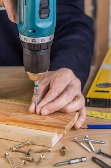 Carpentiere con un cacciavite elettrico. falegname al lavoro fatto a mano.
