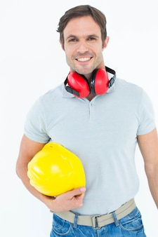 Carpentiere felice con elmetto e protezioni per le orecchie