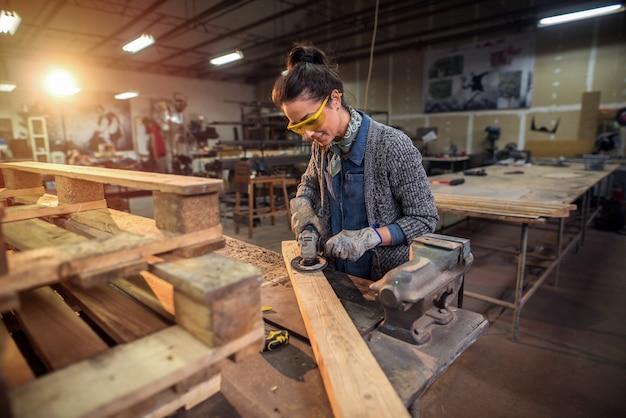 Carpentiere femminile professionista di mezza età che lavora con la carta vetrata nella sua officina