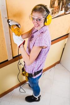 Carpentiere femminile sul lavoro facendo uso della perforatrice della mano