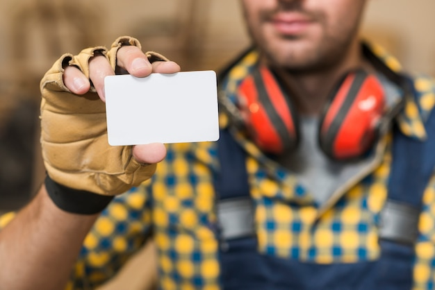 Carpentiere maschio che mostra biglietto da visita bianco in bianco
