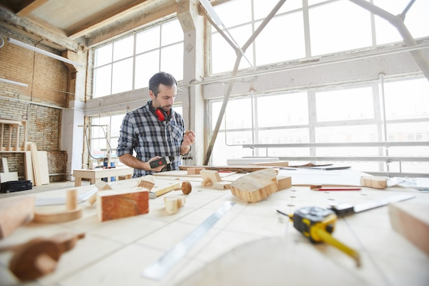 Carpentiere maturo che lavora con il fondo di legno