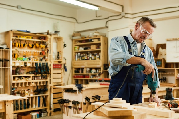 Carpentiere maturo drilling wood