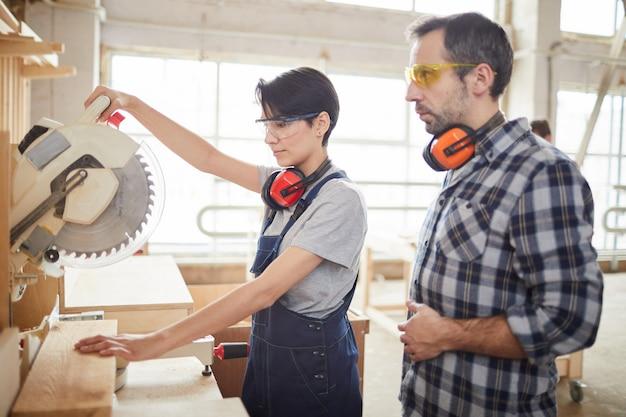 Carpentiere maturo helping trainee in workshop