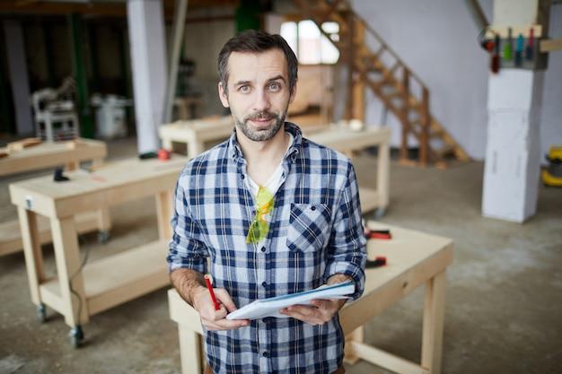 Carpentiere maturo in posa in officina