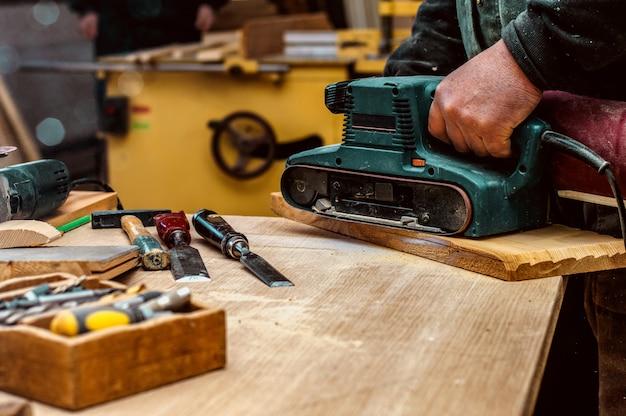 Carpentiere professionista levigatura e finitura di superfici in legno.