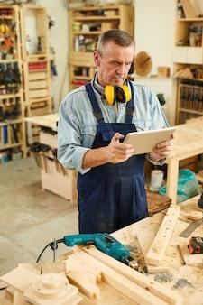 Carpentiere senior che per mezzo della compressa di digital