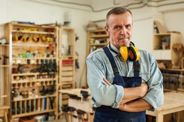 Carpentiere senior che posa nell'officina