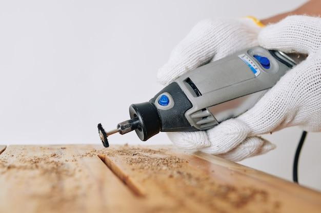 Carpentiere utilizzando lo strumento manuale rotante