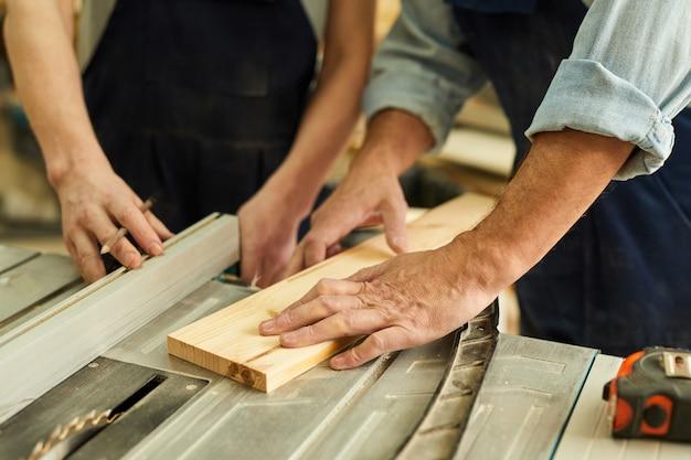 Carpentieri che tagliano primo piano di legno