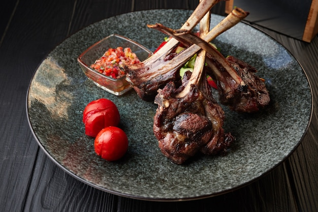 Carré di agnello su un piatto scuro con pomodori e salsa