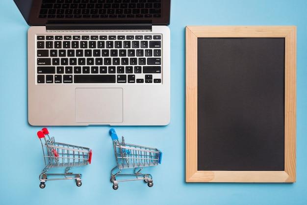 Carrelli del supermercato vicino al computer portatile e cornice per foto