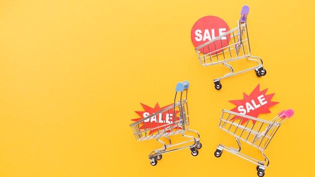 Carrelli della spesa che tengono i distintivi di vendita